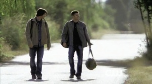 Sam and Dean walk along a deserted road.
