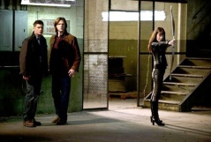 Artemis aims her bow and arrow as the Winchesters look on.
