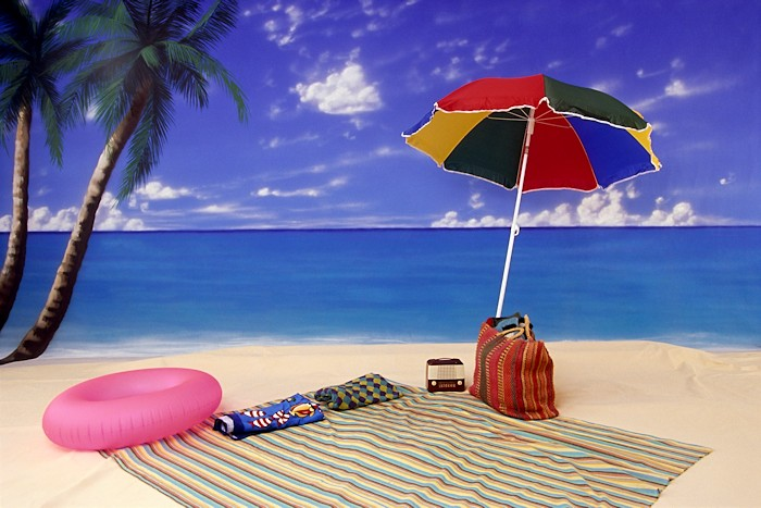 A beach umbrella, pink inner tube, and beach towel are set near the water.