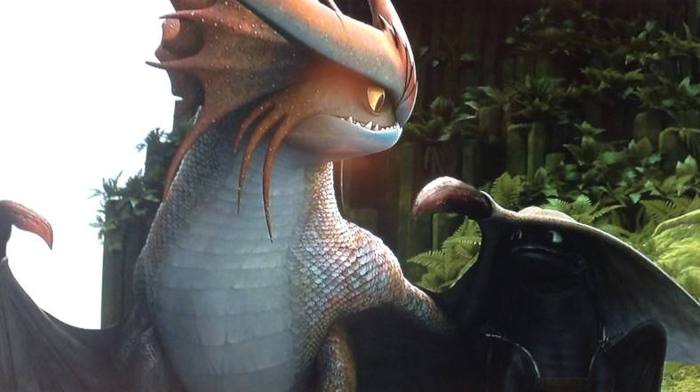 In a scene from How to Train Your Dragon 2, Toothless plays with a large, colorful dragon.